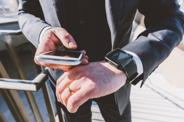 Businessman using smartphone and smart watch