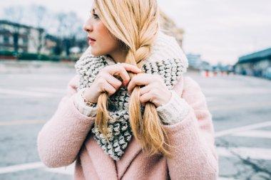blonde woman weaving hair on braid