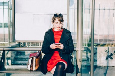 woman sitting at bus stop using smartphone