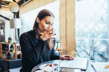 woman sitting in bar with laptop