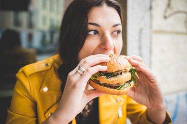 woman sitting  eating an hamburger