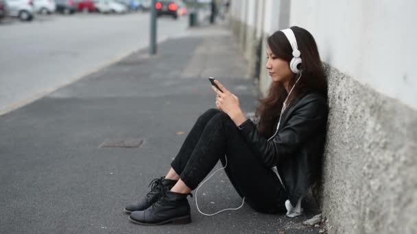 asiatic woman on floor listening music