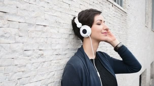 woman leaning against wall, listening music