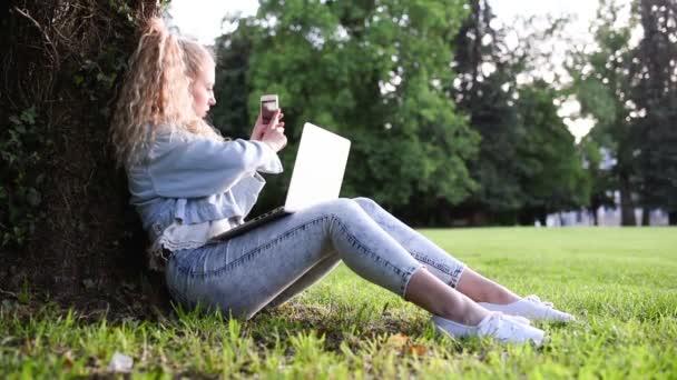 Blondine auf Gras mit Smartphone