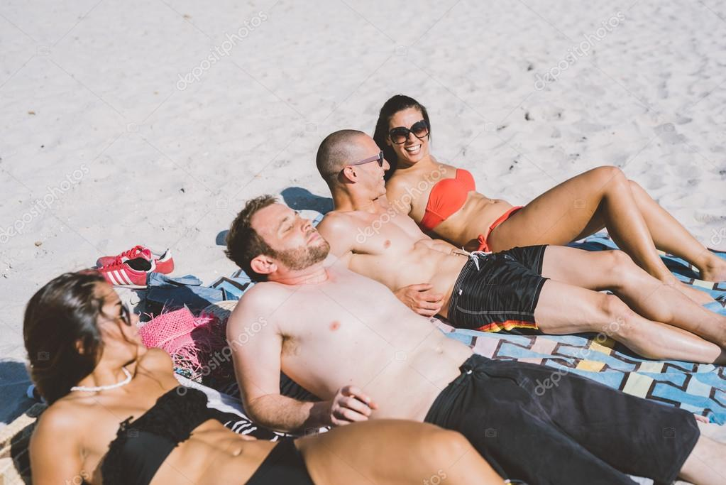 multiethnic friends sunbathing on the beach