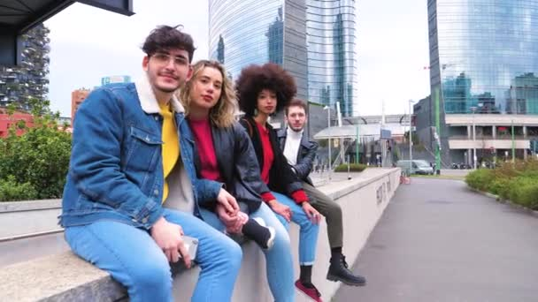 Group of four people friends tourist multiethnic sitting outdoor looking camera smiling enjoying time together having fun staying on vacation sightseeing in the city