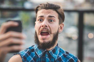 Bearded man taking selfie in the city