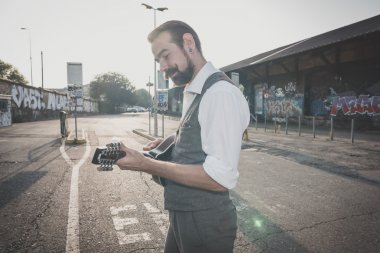 Hipster man playing mandolin