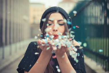 beautiful young woman blowing confetti