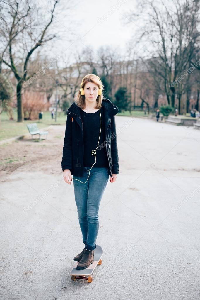 5bcea67bc501d Junge schöne Hipster sportliche blonde Frau in der Stadt mit Skate- und  Kopfhörer — Foto von ...