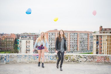Two beautiful girls playing with balloons