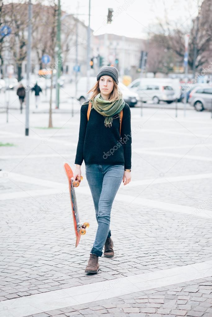 b8953fac17e89 Junge schöne Hipster sportliche blonde Frau zu Fuß in die Stadt mit ihren  Skate
