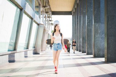 Beautiful asiatic skater woman in city