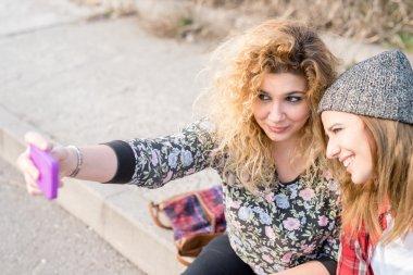 women using smartphone, taking selfie