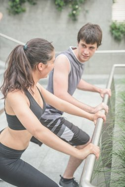 Couple stretching leaning against an handrail