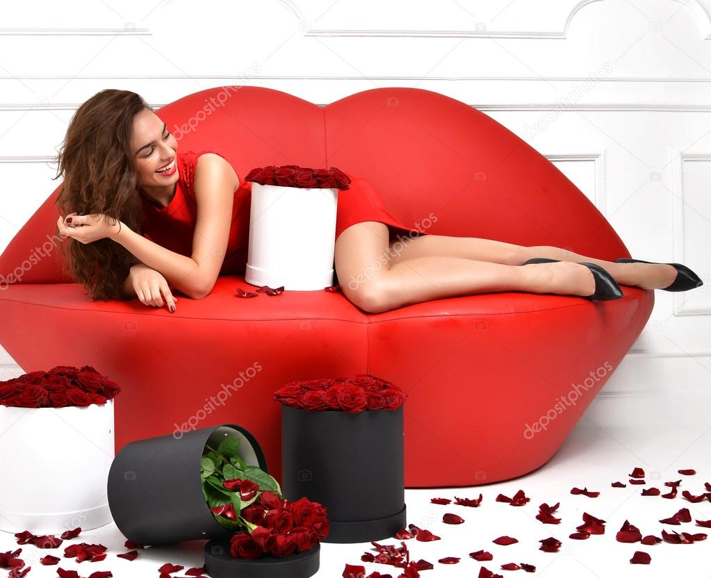 Beautiful Luxury Fashionable Woman Lying On Red Lips Sofa Couch And Red  Dress With Roses Bouquet And Petals Laughing U2014 Photo By Dml5050