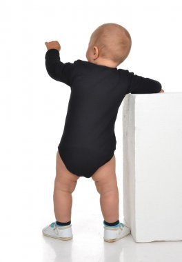 Rear view of caucasian one year infant baby boy toddler kid stan