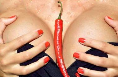 Closeup woman boobs breast with red hot chili pepper between in