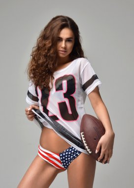 Sexy happy Fierce young woman Football Player with ball standing