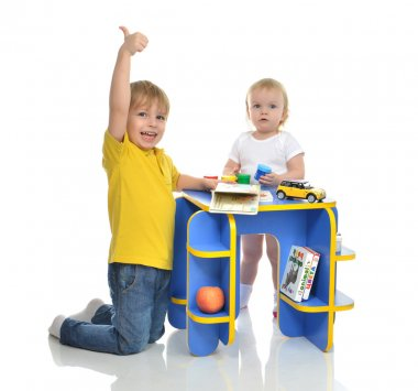 Two children little toddler girl and a funny baby boy brother an