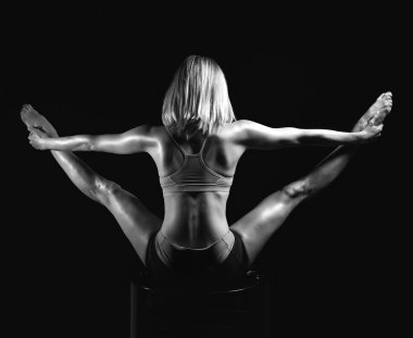 Young sport yoga woman back view posing while doing gymnastic sp