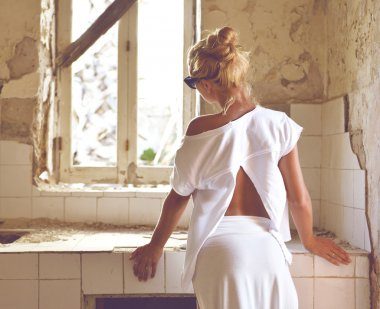 Young woman thinking of remodeling old house kitchen