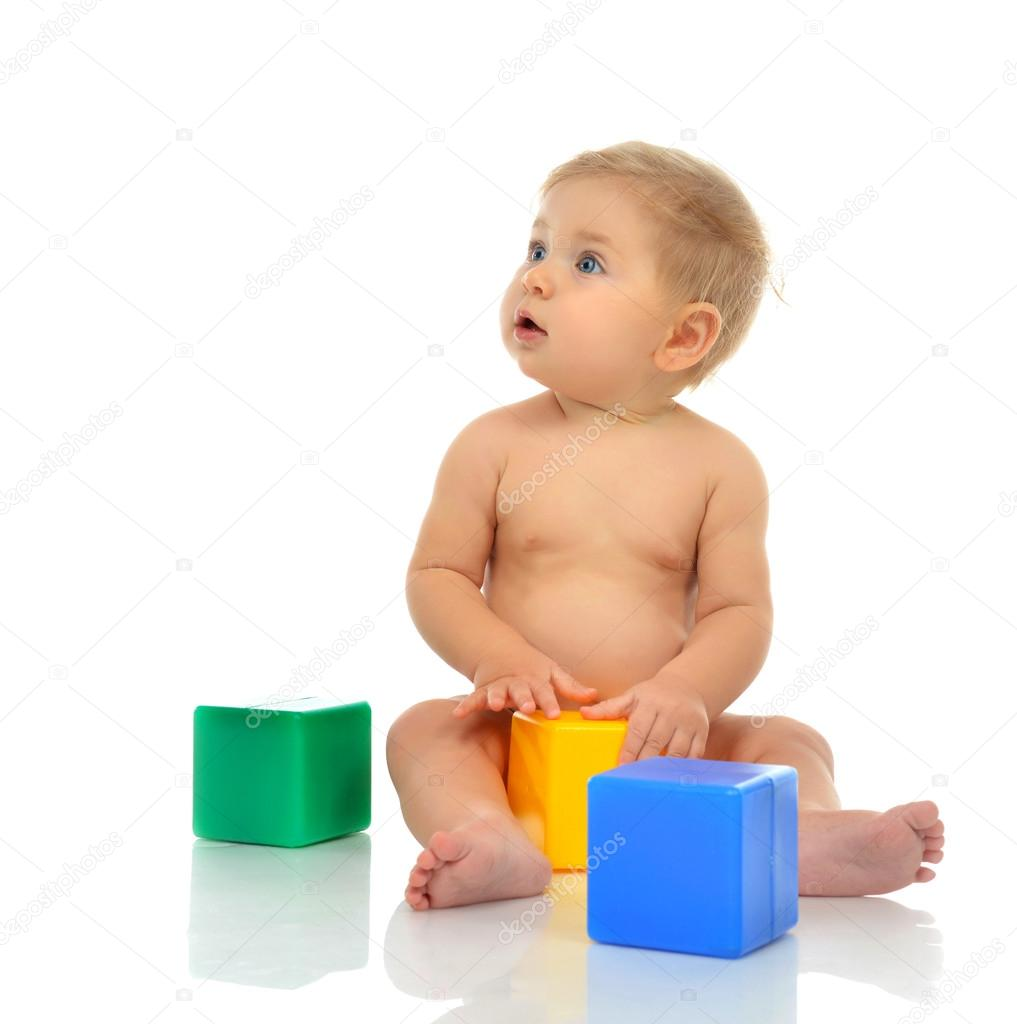 fa18dcb75 Infant child baby boy toddler playing holding green blue yellow — Stock  Photo