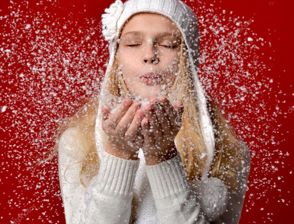 Bastante joven de sombrero blanco que sopla sobre la nieve en su manos  sobre fondo rojo — Foto de dml5050 708d3506178