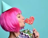 Fotografie Schöne lustige Mode fröhliche Frau in heiße Rosa Party Perücke Essen