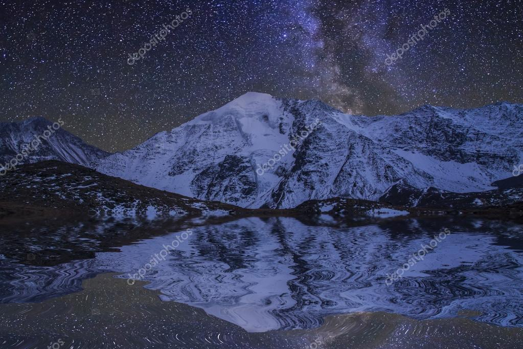 Amazing night landscape with mountains and stars. Reflection of