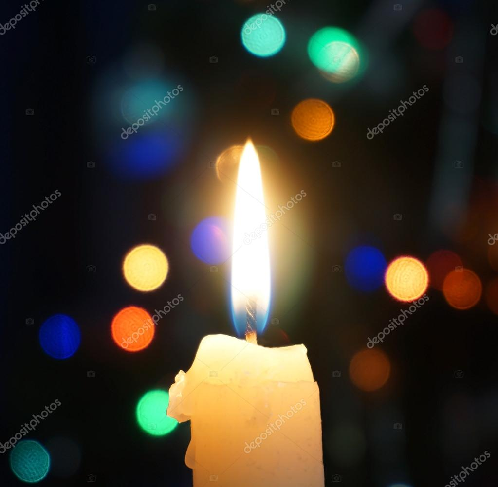 Burning candle on a background of Christmas lights