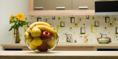 bowl with healthy fruits in kitchen