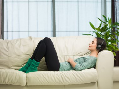 Side view of young caucasian woman lying on sofa and listening to music with headphones stock vector