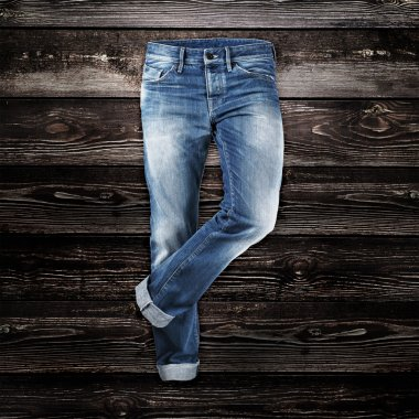 Jeans trouser over dark wood planks background stock vector