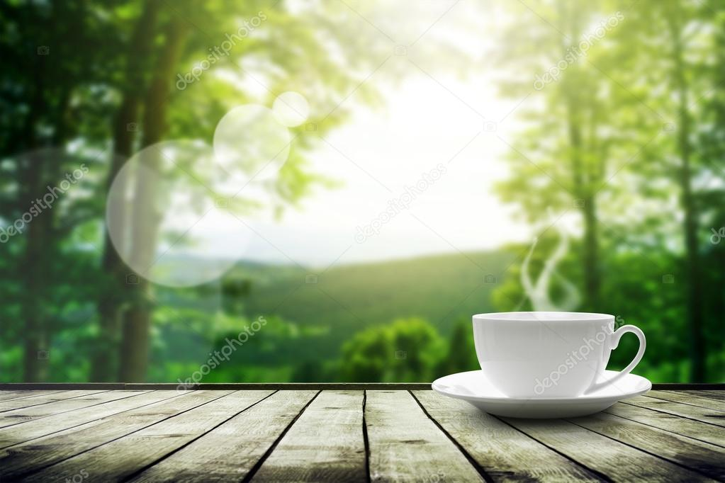Cup with tea on table over mountains landscape with sunlight