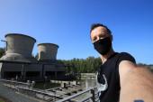 Touristen-Selfie mit Gesichtsmaske im Industriegebiet von Bochum. Reisende-Selfie mit ehemaligem Kraftwerk im Stadtteil Stahlhausen.