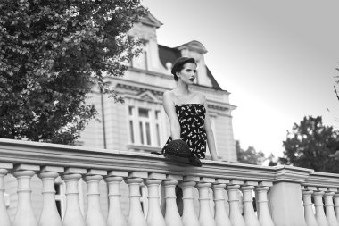 very nice woman , standing near parapet, BW shot