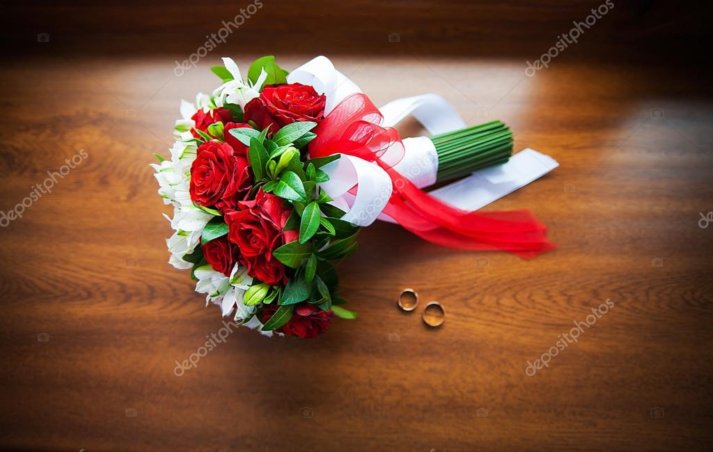 Beautiful wedding bouquet and rings on wood