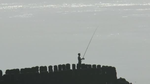 Rybář na vlnolamu v řece Scheldt v ranní mlze