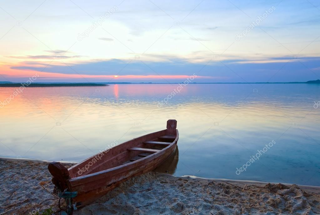 Sunset with boat near the summer lake shore