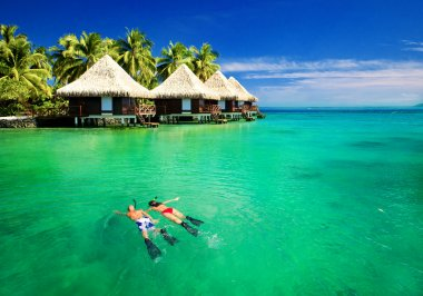 Couple snorkling in lagoon with over water bungalows
