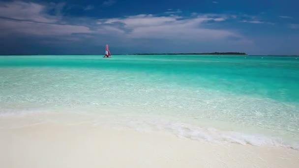 Plachetnice s červenou plachtou na pláži pustém tropickém ostrově