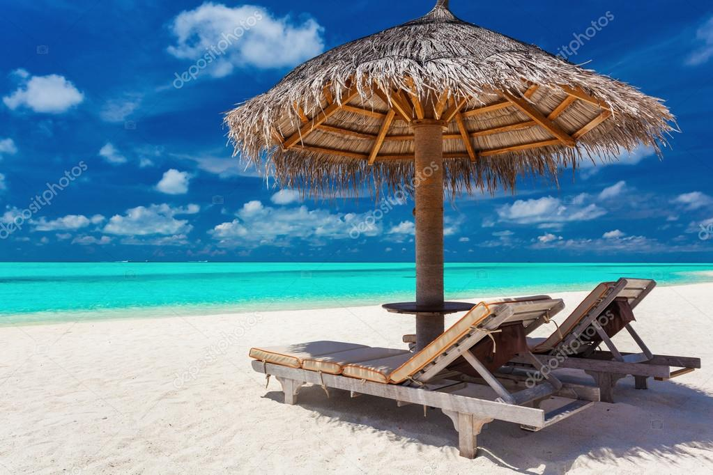 Two chairs and umbrella on a tropical beach