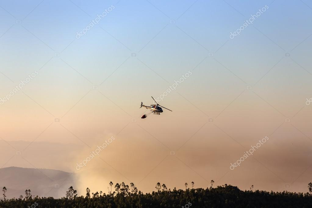 fire-fighting helicopter with a water bucket fighting a fire on