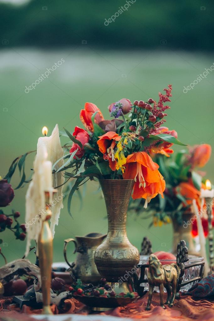 Candels and red flowers. Boho decor of table. Photography made in the style of fine art. Stylized like film photo