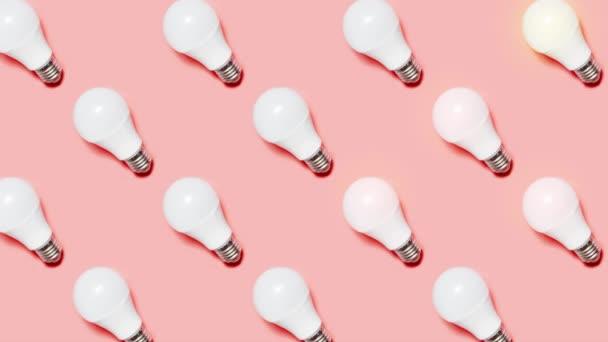 Kreative Stop-Motion-Animation. Beleuchtung von LED-Lampen auf rosa Hintergrund. Das Konzept der Ökoenergie oder Brainstorming für Unternehmen.