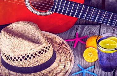 Acoustic guitar hat starfish and glass of tasty fresh lemonade with lemons  on vintage wood summer background