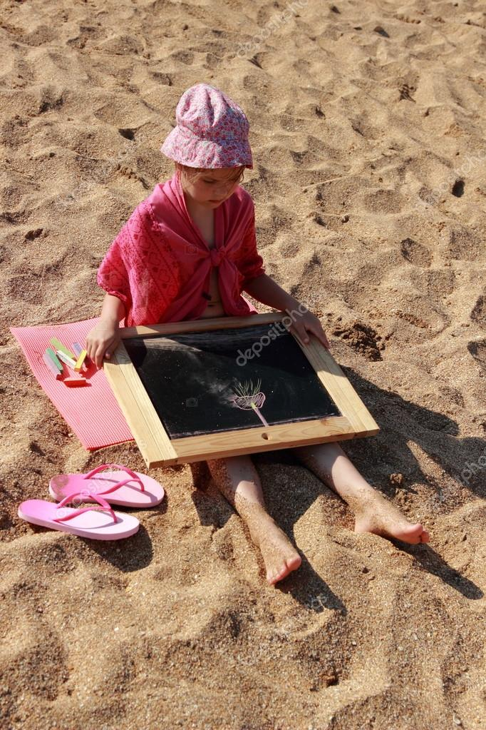 Kid drawing on the beach
