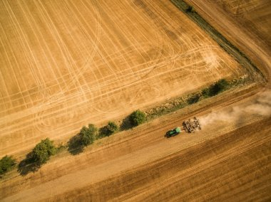 Aerial view of a tractor working a field after harvest