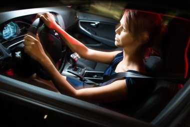 Driving a car at night - pretty, young woman driving her car